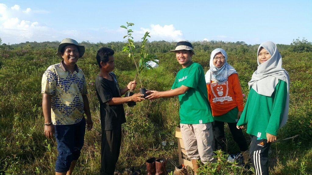 Foto Penyerahan Bibit Pohon secara Simbolis dari Relawan LindungiHutan Palembang kepada Masyarakat sekitar pada Penanaman RawatBumi di Ogan Komering Ilir, Sumatera Selatan/Motivasi Menjadi Relawan
