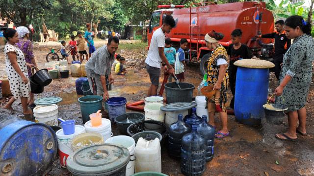 Sejumlah warga menunggu giliran pembagian jatah air bersih yang dibagikan petugas BPBD Kabupaten Serang di Kampung Wadasturus, Sindangsari, Serang, Banten, Jumat (23/8). © ANTARA FOTO/Asep Fathulrahman