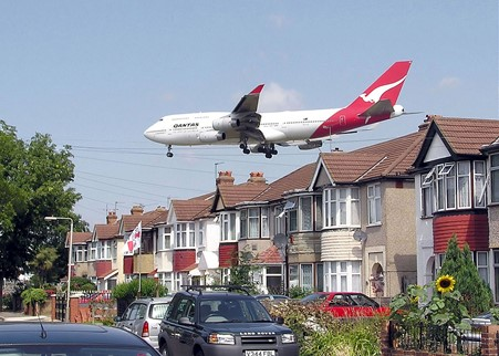 Gambar 3. Qantas Boeing 747-400 passes close to houses shortly before landing at London Heathrow Airport. ©️ Wikipedia